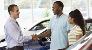 Jamaican couple shaking man arm after buying car